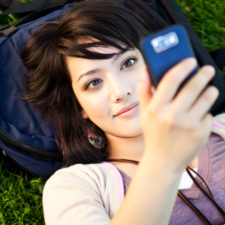 Girl laying on the grass looking up at a cell phone