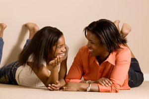 Photograph of two teen girls talking and smiling.
