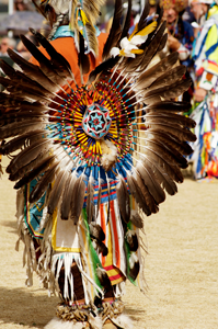 Photograph of a young person dressed in traditional Native American clothing, including beads and feathers.