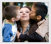 Two kids kissing their mother
