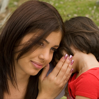 Mother listens to daughter tell a secret in her ear