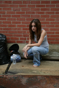 Photograph of a teen girl crouching on the sidewalk, wearing torn jeans and no shoes.