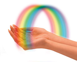 Photograph of two hands with a rainbow arched over them.