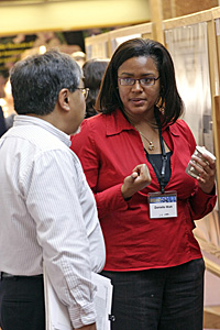 Woman talking to scientist in front of science project