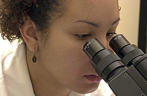 Woman scientist looking into microscope