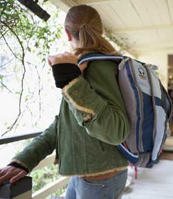 Photograph of a young person leaving a house and carrying a backpack.