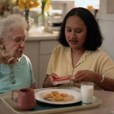 Photograph of a senior woman eating lunch with a caregiver