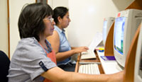 Two women seated at computer work stations view information on monitors