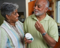 A couple holding a dietary supplement pill