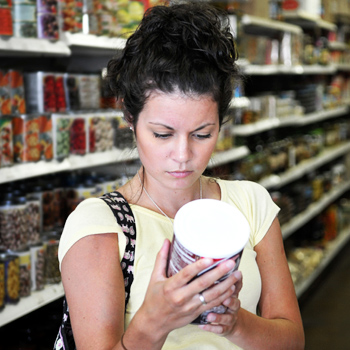 Have Food Allergies? Read the Label - Woman reading nutrition facts label in grocery store