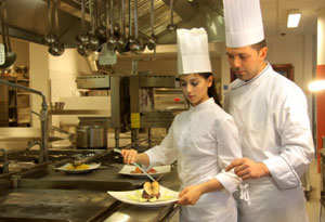 Photograph of a chef instructing an apprentice chef.