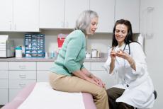 Fotografía de una doctora explicando el uso de medicamentos a una paciente