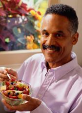 Fotografía de un señor comiendo una ensalada de frutas