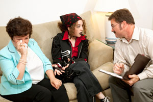 Photograph of a young woman and her mother talking to a therapist.