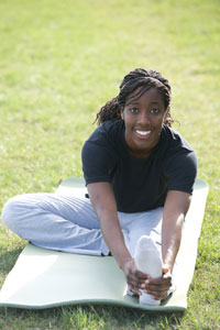 Photograph of a young woman smiling and doing yoga.