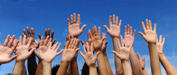 Photograph of diverse raised hands.