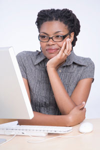Photograph of a woman looking at a laptop computer.