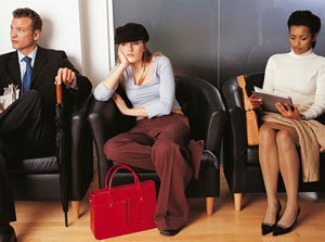 Photograph of a bored looking teen girl sitting between two adults waiting for a job interview.