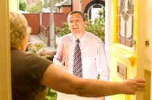 Photo of an untrustworthy man in a senior's doorway.