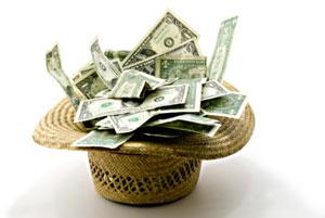 Photograph of a hat full of dollar bills.