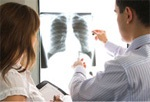 Medical professionals look at x-ray film on a lightbox.