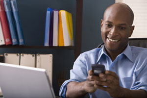 Photograph of a smiling man making a telephone call.