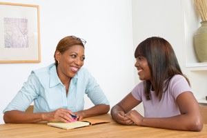 Photograph of a woman talking with a teen girl. Both are smiling.