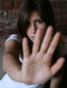 Photograph of  a teen girl standing with her back against a brick wall while holding up her hand in self-defense,