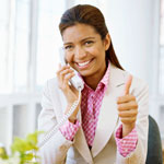 Photograph of a young person talking on the phone and giving the thumbs up gesture.