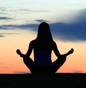 Silhouette of a young woman meditating.