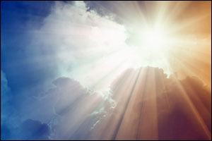 image of bright sun with beams, dark clouds