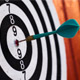 Photograph of a dartboard with a dart at the center of the board
