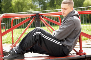 Photograph of a young man sitting in a playground looking sad.