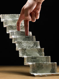 """Photograph of a dollar bill folded into steps, with fingers """"walking"""" up the steps."""