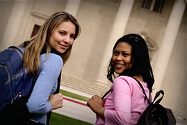 Two teen girls with backpacks walking on a school campus