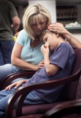 Photograph of a mother sitting in a doctors waiting room with her son who has hurt his nose