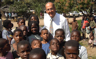 Fogarty Director Dr Roger I Glass with a large group of African children, posing for camera