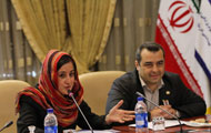 Woman wearing head scarf and man seated at conference table, woman speaks into microphone, Iranian flag in background