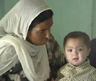 Pakistani woman seated watches a boy toddler on her lap