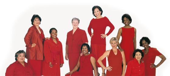 Grupo de mujeres sentadas y de pie con vestidos rojo.