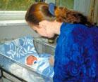 woman nurse bends over a newborn in a plastic hospital crib