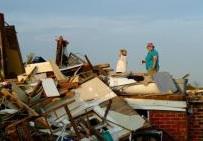 Dos mujeres hija revisan los daños ocasionados a su hogar después de que un tornado destruyera la vivienda