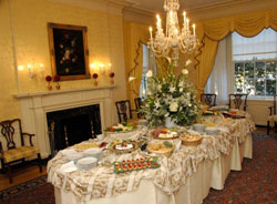Dining room, lit by chandelier, with table filled with serving dishes of food, fireplace in the background