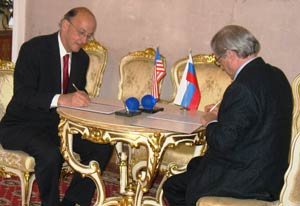 Dr Roger I Glass signs agreement on table, Russian representative across table signs, US and Russian flags on table