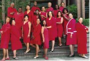 A crowd of women of varying ethnicities, ages, and body types wearing red dresses and red skirts pose on stairs.