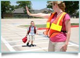A crossing guard helps a child.