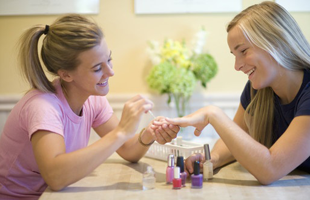 A girl giving her friend a manicure