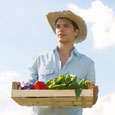 Photograph of a young man wearing a straw hat and carrying a box of produce.