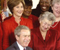 Image of then President George W. Bush, Heart Truth Founding Ambassador Laura Bush, and heart disease survivors in red dresses, signs an American Heart Month Proclamation on February 2, 2004.