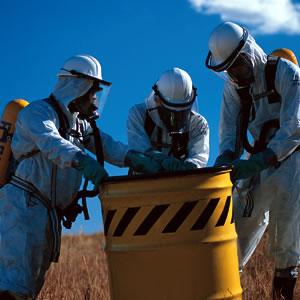 three hazardous waste workers with barrel